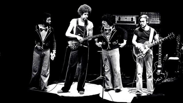 Vier Männer auf der Bühne, einer spielt Bass, der andere E-Gitarre.