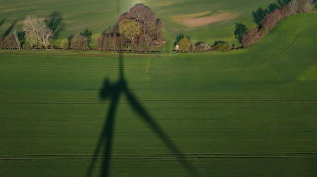 Der Schatten eines Windrads auf einer Wiese.