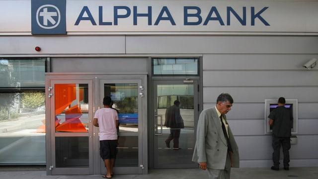 Eine geschlossene griechische Bank, Menschen, die am Bankomat Geld abheben.