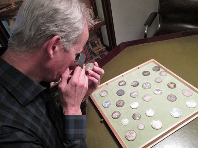 Mann betrachtet durch eine Lupe eine Münze.