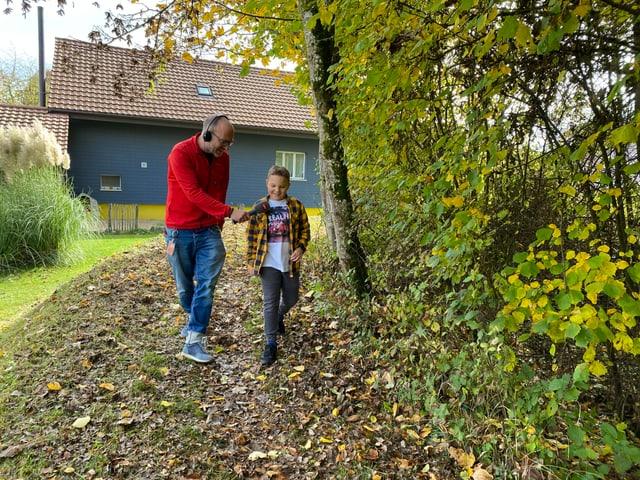 Noa und Reto spazieren durch den Wald.