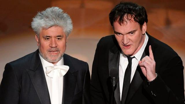 Pedro Almodóvar und Quentin Tarantino halten eine Laudatio während einer Preisverleihung.