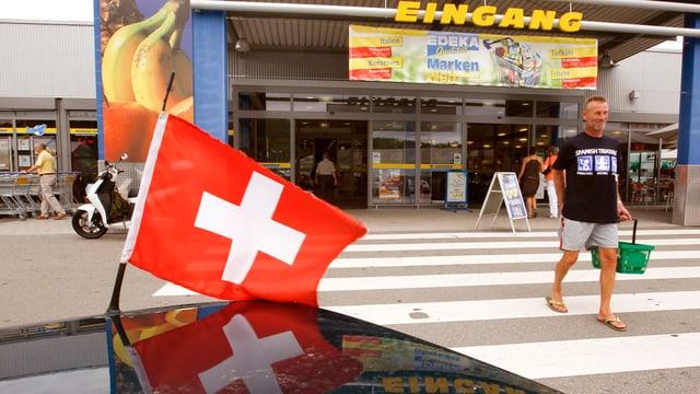 Eine Schweizer Flagge vor dem Eingang eines Deutschen Warenhauses
