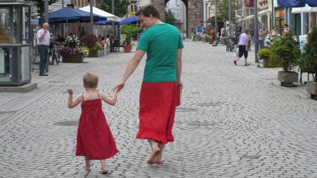 EIn Mann mit grünem Shirt und rotem Rock geht mit einem jungen in einem roten Kleid durch eine Strasse