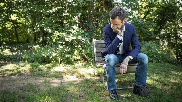 Autor Thomas Meyer in Denkerpose auf einem Holzstuhl.
