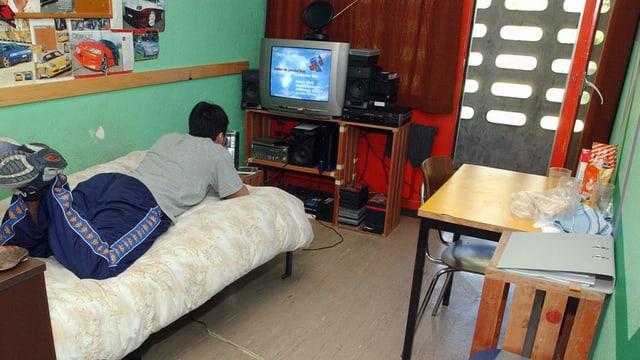 Jugendlicher im Zimmer auf Bett