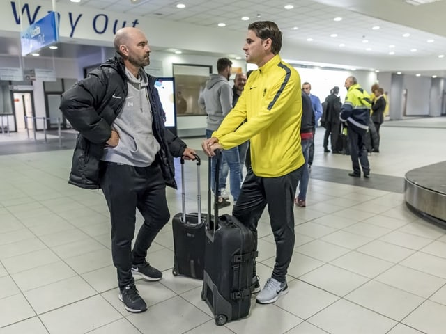 Joël Magnin und Gerardo Seoane stehen am Flughafen mit je einem Koffer.