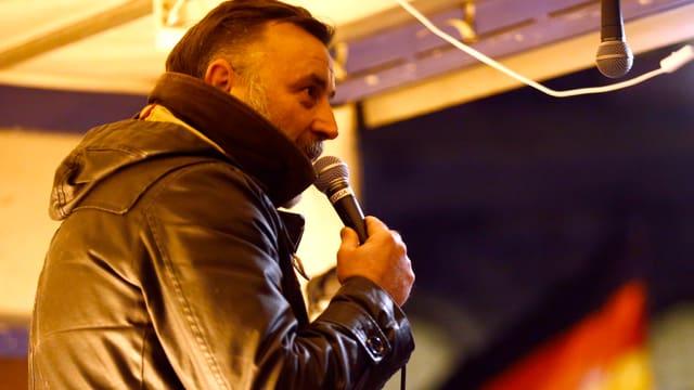 Ein Mann in Lederjacke spricht in ein Mikrofon.