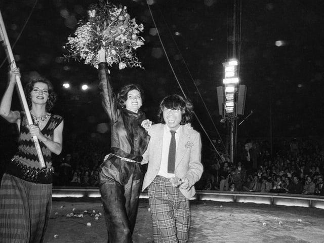Drei Menschen in einer Zirkusmanege