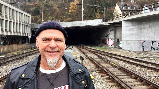 EIn Mann mit Ziegenbart, Lederjacke und Wollmütze steht lächelnd auf einem Bahngleis.