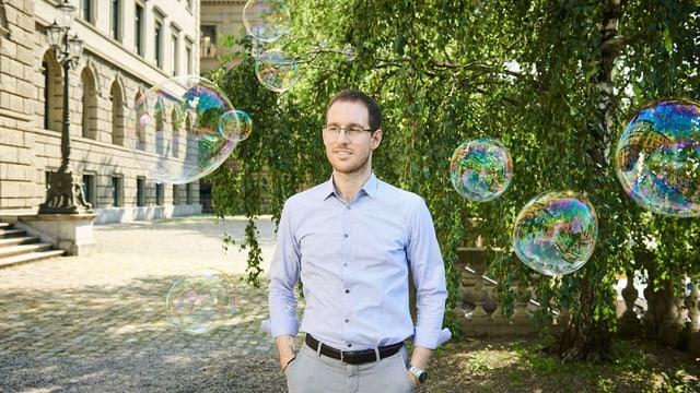 Ein Mann steht auf einem Kiesplatz, um ihn fliegen Seifenblasen.