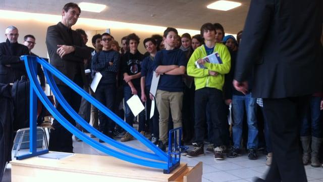 Eine Schulklasse steht vor einem Ausstellungsobjekt.