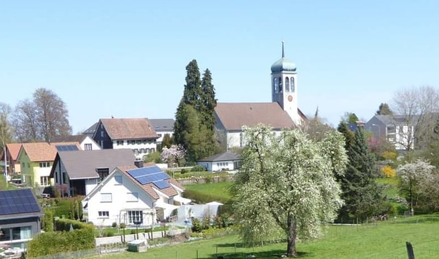 Ortsbild mit Kirche und Apfelbäumen.