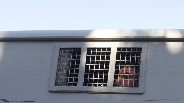 Gefangener schaut durch die Gitterstäbe eines Gefangenenfahrzeugs.