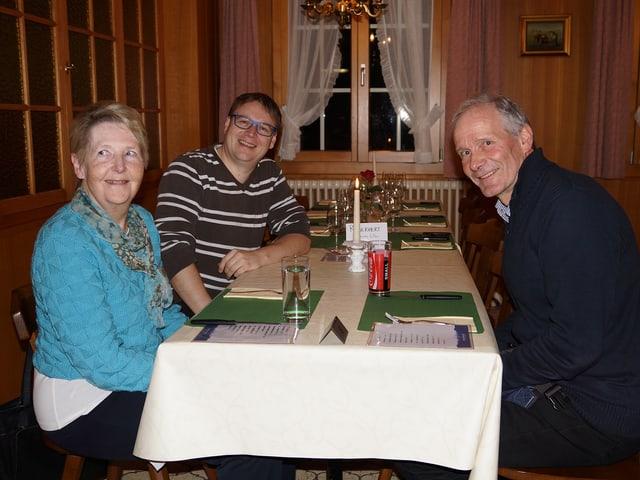Eine Frau und zwei Männer an einem gedeckten Tisch in einer Gaststube.