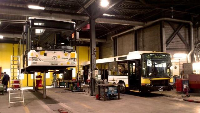 Zwei Busse mit unterschiedlichen Beschriftungen in einem Depot