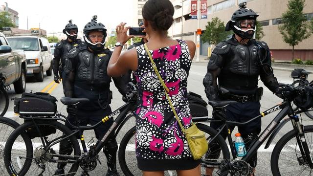 Eine Frau fotografiert Polizeikräfte in voller Montur mit Mountainbikes.