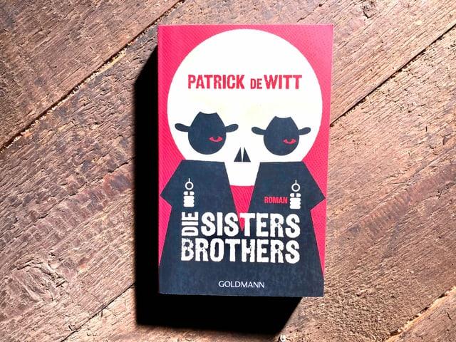«Die Sisters Brothers» von Patrick deWitt liegen auf einem dunklen Dielenboden