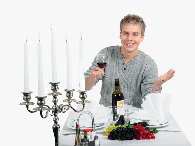 Reto Scherrer mit Weinglas am Tisch.
