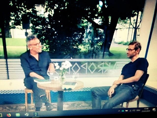 Ein Foto von Tom Kummer und Christoph Höhtker, die an einem Tisch sitzen und miteinander diskutieren.