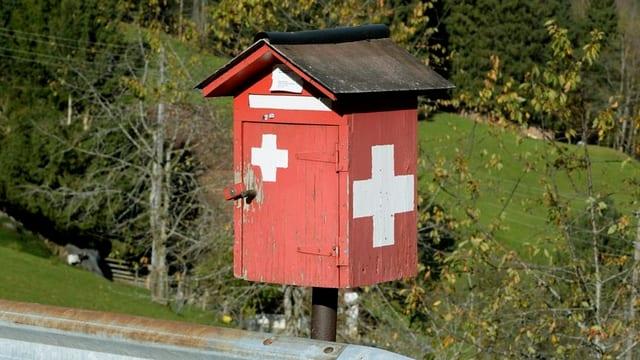 Roter Briefkasten mit Schweizerkreuzen.