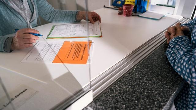An einen Schalter füllt eine Frau verschiedene Papiere aus.