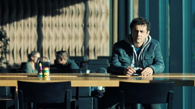 Ein Mann sitzt einsam an einem Tisch in einem Restaurant.
