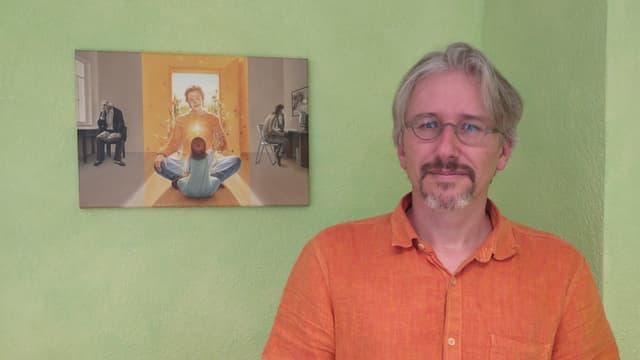 Mann mit Brille steht vor einer grünen Wand.