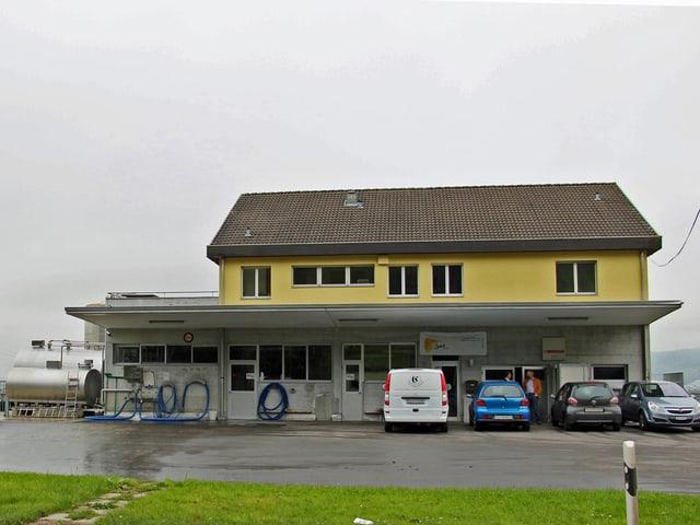 Die Käserei in Kottwil. Ein gelbes Gebäude. Auf dem Vorplatz stehen mehrere Autos.