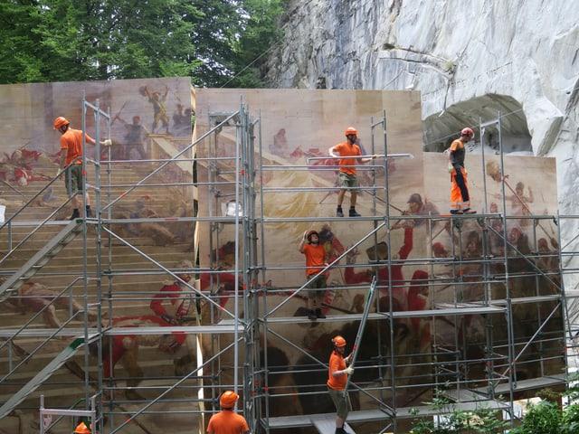 Ein riesiges historisches Gemälde wird vor dem Löwendenkmal in Luzern aufgebaut.