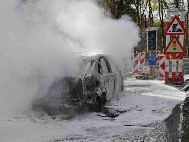 Ausgebranntes Auto vor Ampel.