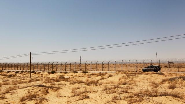 Ein Fahrzeug fährt einen Grenzzaun entlang, dahinter die Wüste Sinai.