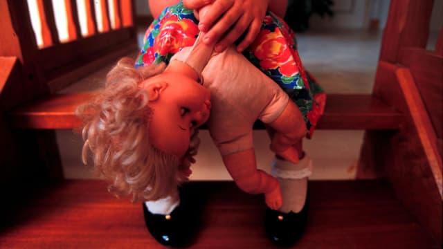 Mädchen mit Puppe auf einer Treppe.