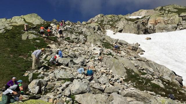 Erwachsene und Kinder hämmern und graben an einem Berg.