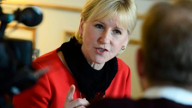 Wallström, blond in rotem Kleid, spricht zu einem Mann, der nur von hinten zu sehen ist, eine TV-Kamera ist auf sie gerichtet.