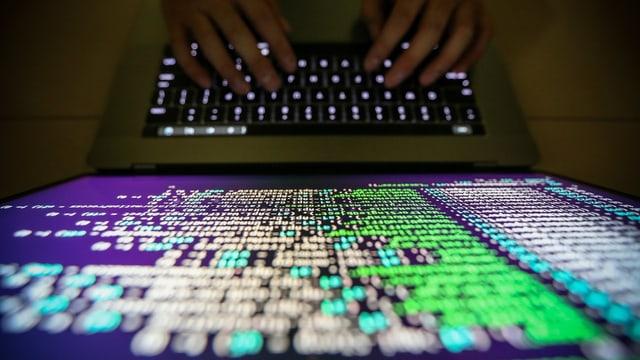 Purtret d'in computer e mauns che scrivan sin la tastatura.