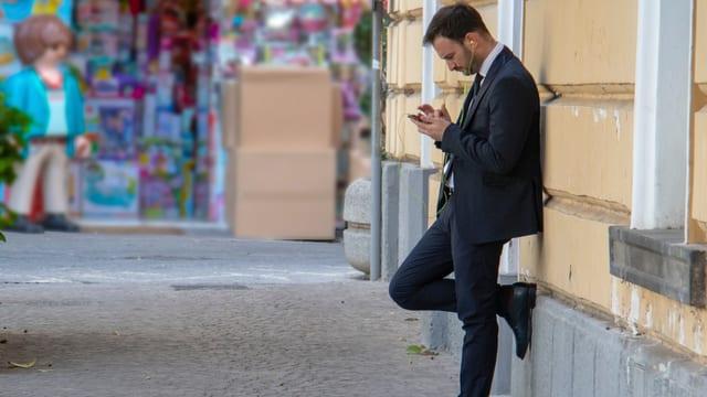 Mann im Anzug mit Smartphone und Kopfhörern lehnt an einer Hauswand.
