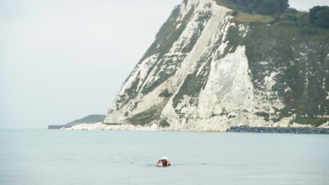 Ein Mann schwimmt im Meer. Im Hintergrund ist ein Gebirge.