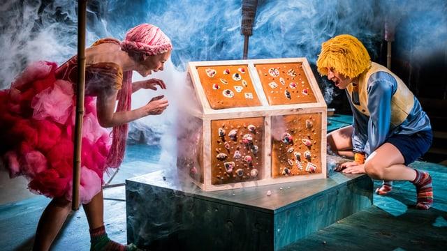Szene aus der Märchenoper Hänsel und Gretel mit einem Lebkuchenhaus in der Mitte.