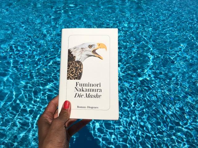 Annette König hält das Buch von Fuminori Nakamura: «Die Maske» vor blaues Wasser
