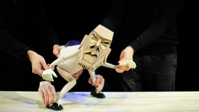 Eine Puppe wird von drei Menschen gleichzeitig animiert. Man sieht lediglich deren Hände