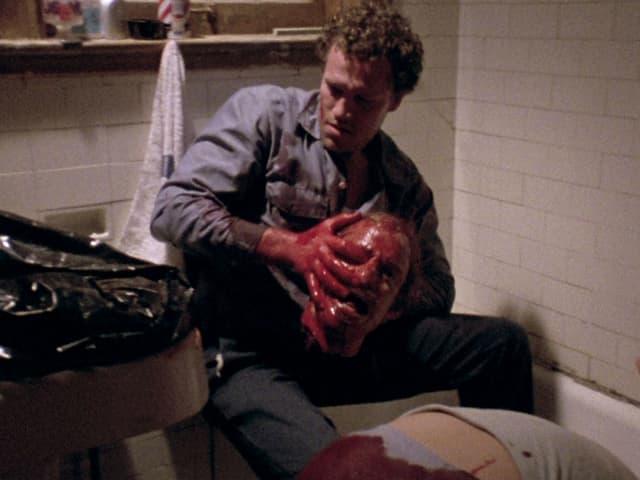 Männ hält blutigen Kopf in den Hänen, der Körper dazu hängt aus der Badewanne.