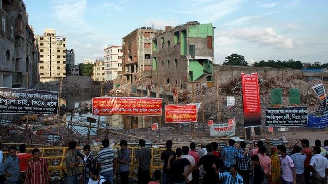 Menschen betrachten eine Baugrube.