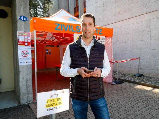 Götte steht vor einem Pavillon mit der Aufschrift Zivilschutz