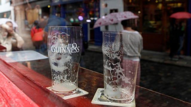 Zwei leere Biergläser auf eine Bartheke.