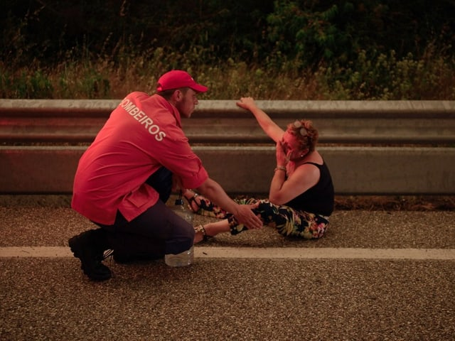 Ein Feuerwehrmann hilft einer Frau, die auf der Strasse sitzt.