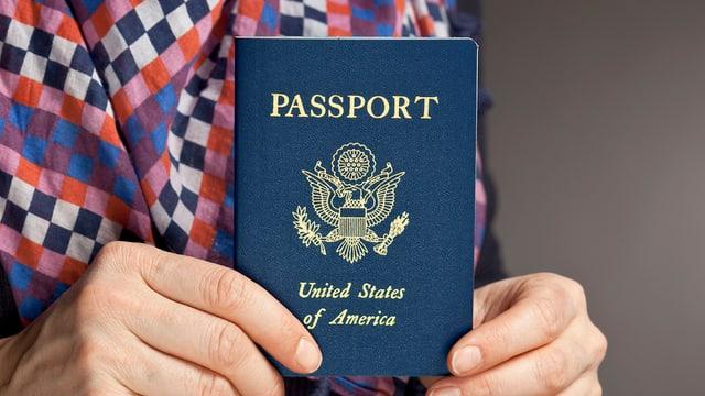 Ein US-amerikanischer Pass, in der Hand gehalten.