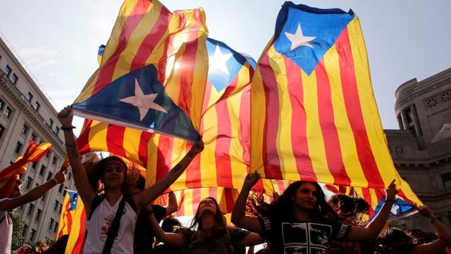 Junge Frauen schwenken Katalonien-Flaggen.
