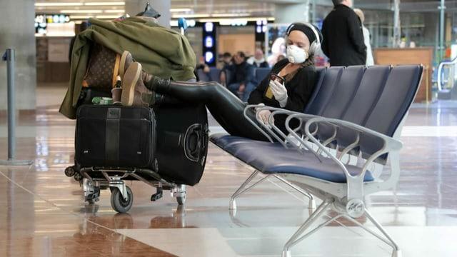 viagiatur cun mascra da protecziun a la plazza aviatica vid spetgar