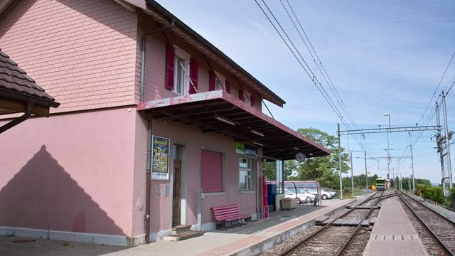 Bahnhofshäuschen mit Regionalzug im Hintergrund
